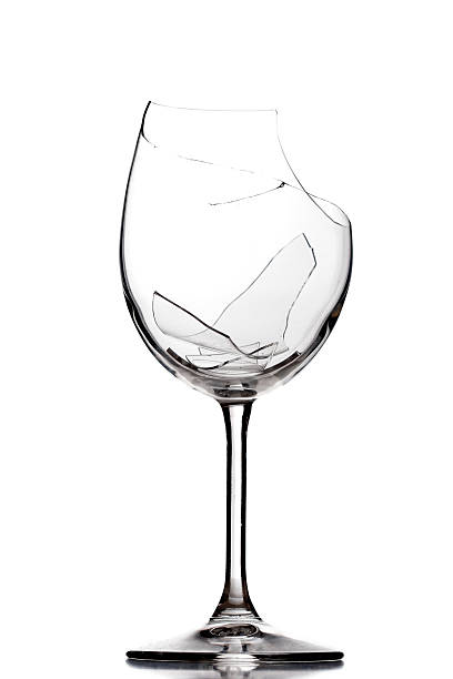 Broken wine glass shattered into pieces stock photo