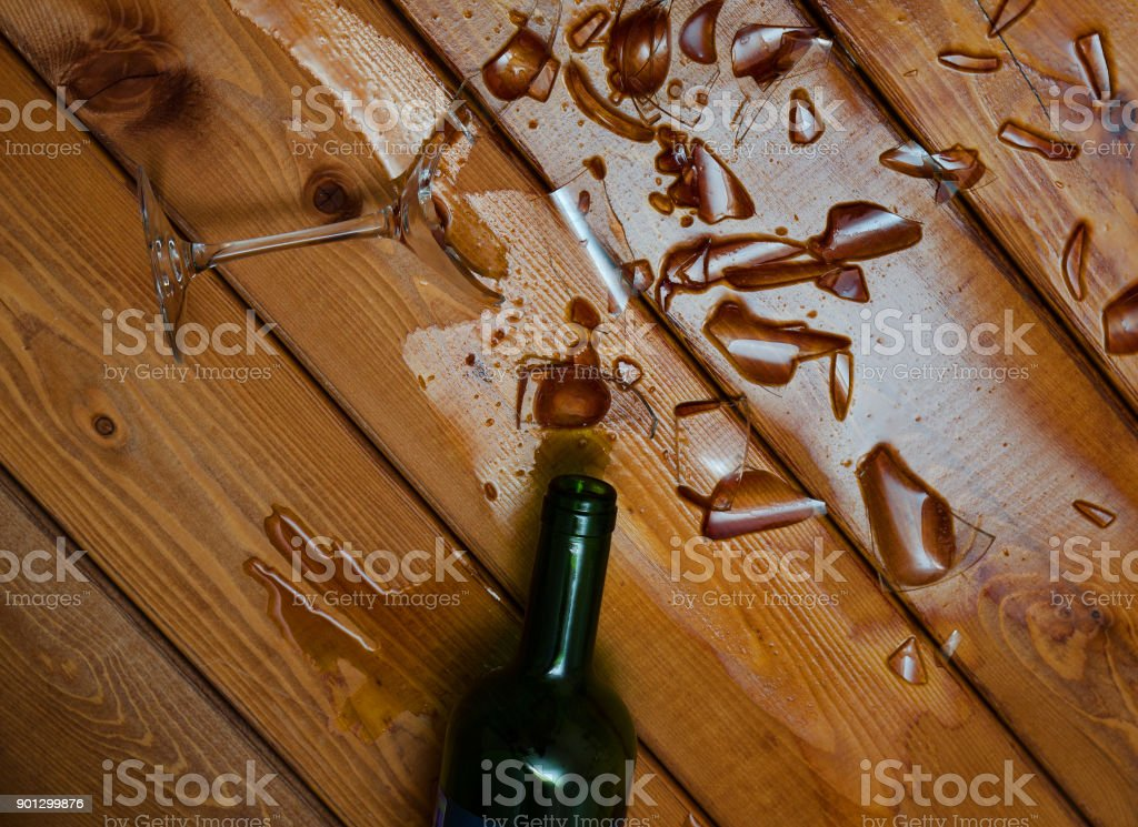 broken wine glass with bottle on  table stock photo