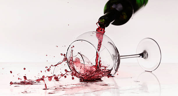 Broken wineglass on the table. Poured red wine, like blood. stock photo