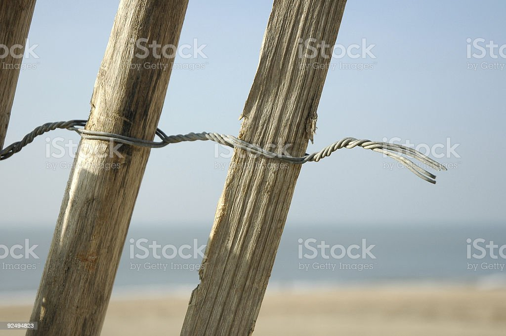 Broken wood and iron fence going to the beach royalty-free stock photo