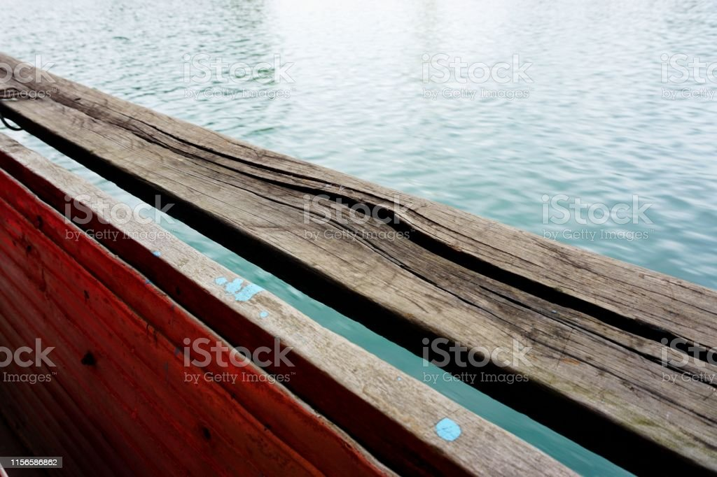 Cracked wooden boat rail contrasts with rippling river abstract...