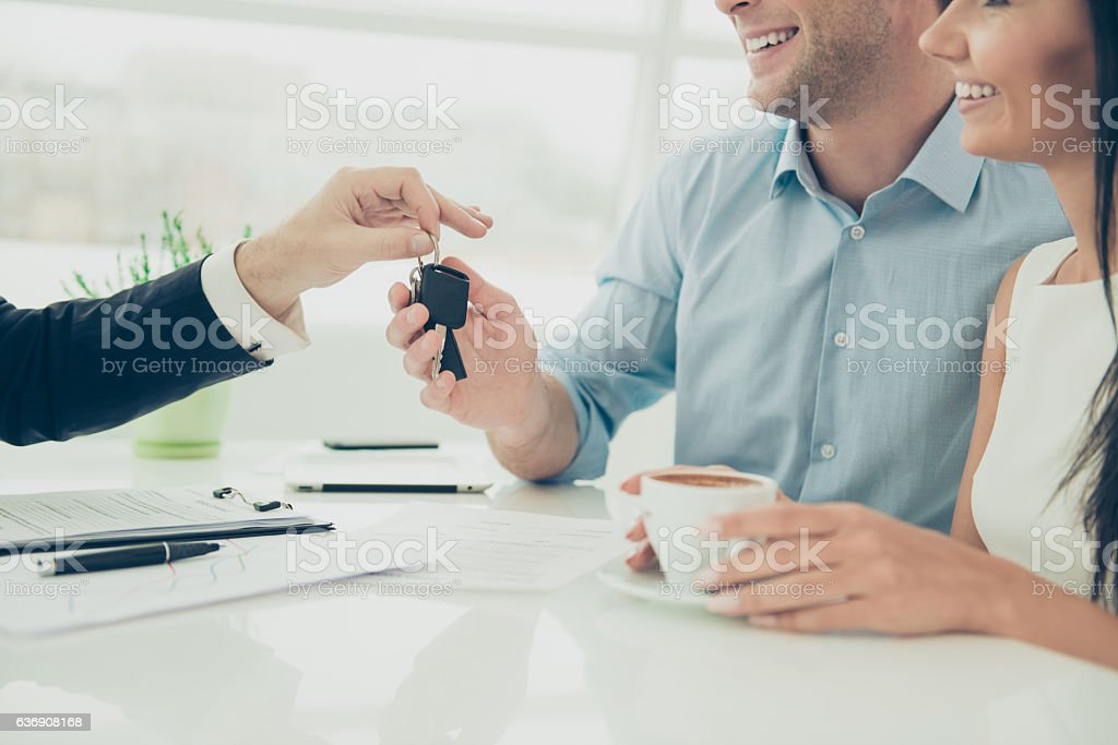 broker giving keys of new house to happy couple - foto de stock