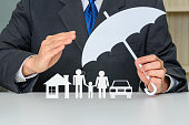 istock Broker / insurer holds an umbrella to protect parents e.g. father, mother, a child, a house and a sedan car 1249609877