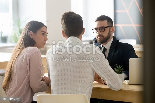 994164754istockphoto Broker listening to clients during office meeting or consultation 994164754