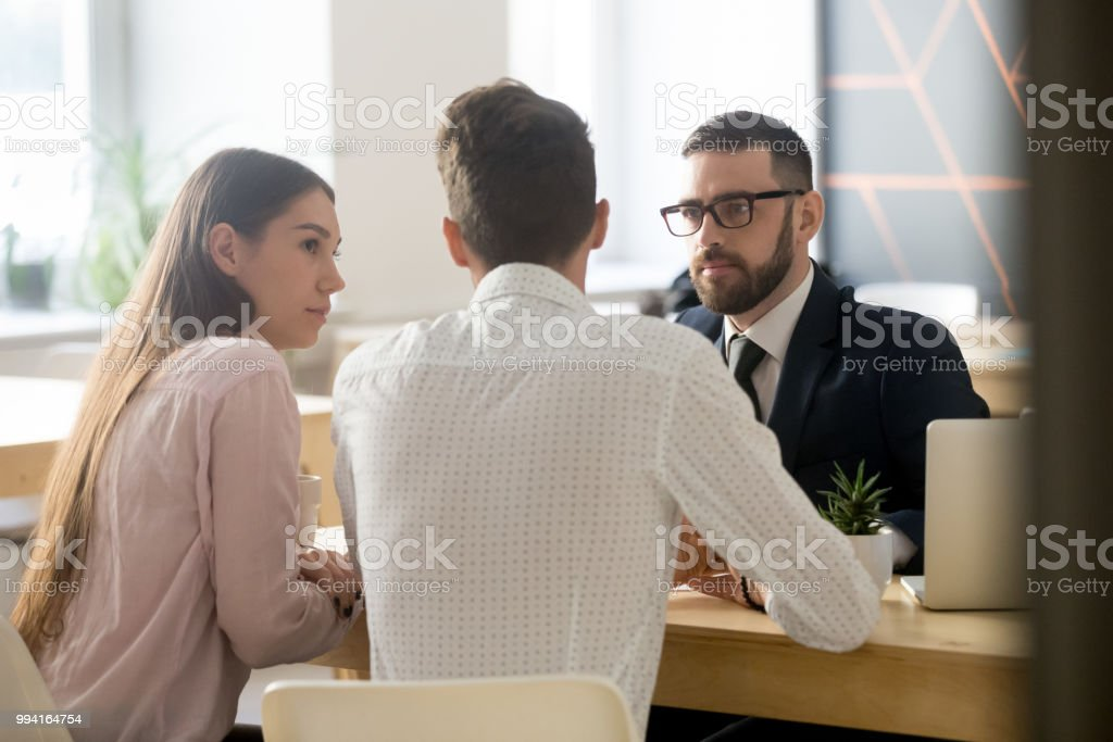 Broker listening to clients during office meeting or consultation stock photo