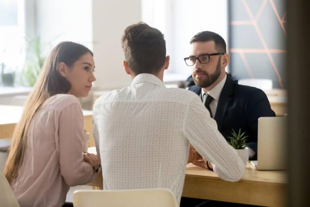 makelaar luisteren naar klanten tijdens office vergadering of overleg - notaris stockfoto's en -beelden