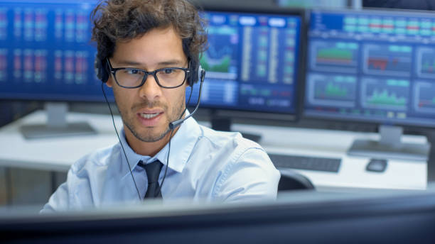 Broker Making Sales with a Headset with His Multi-Ethnic Team of Stock Traders at the Stock Exchange Firm Office is Busy Selling and Buying Bonds and Shares. Displays Show Relevant Graphs and Numbers. stock photo