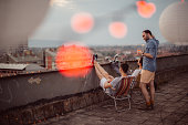 Couple of male friends having a party on the rooftop of the building at sunset, with snacks, drinks and music