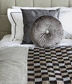 a close up view of silk cushions (one round and one square) on a bed with a square patterned bedspread in the foreground. The colours are shades of silver - grey and bronze.Looking for more images of cushions Then please click on the Lightbox link below...A>A