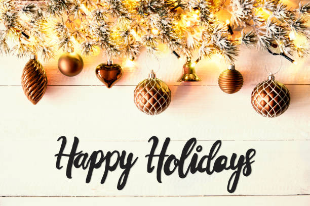 bronze balls, calligraphy happy holidays, fairy lights - happy holidays stock pictures, royalty-free photos & images