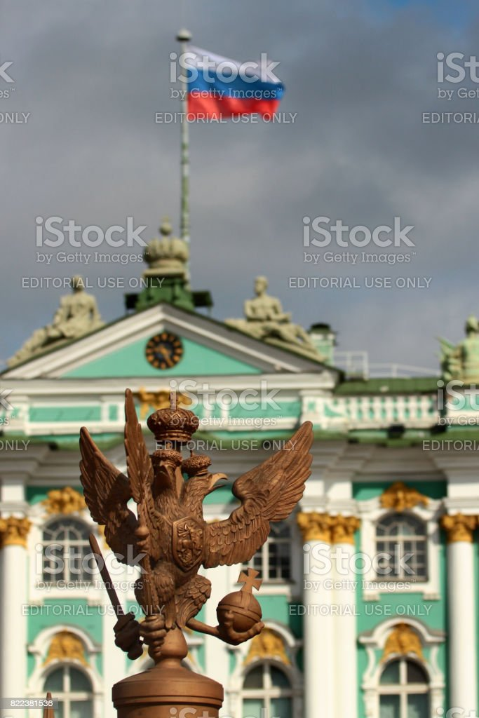 SAINT PETERSBURG, RUSSIA - JULY 5, 2017: Bronze double-headed eagle with sword, orb and cross. Symbol and coat of arms of Russia with Russian banner on Winter Palace. stock photo