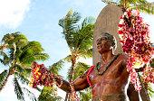 Honolulu, USA - December 11, 2012: The Bronze Duke Kahanamoku statue on Waikiki beach just before sunset covered in traditional Hawaiian leis