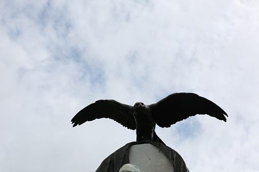 Foto de Estátua De Bronze De Águia Com Asas Espalhar Contra Um Céu Azul Nublado e mais fotos de stock de Animal