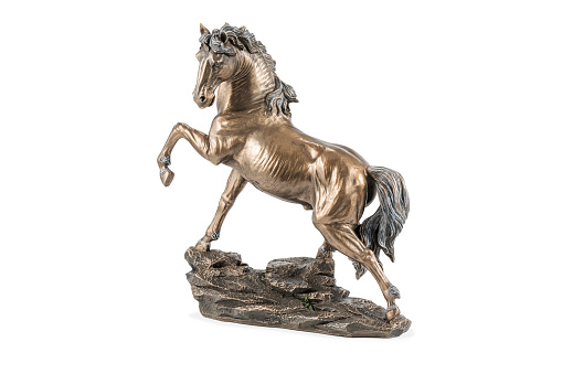 beautiful bronze statuette of a horse with a raised hoof, isolated on white background