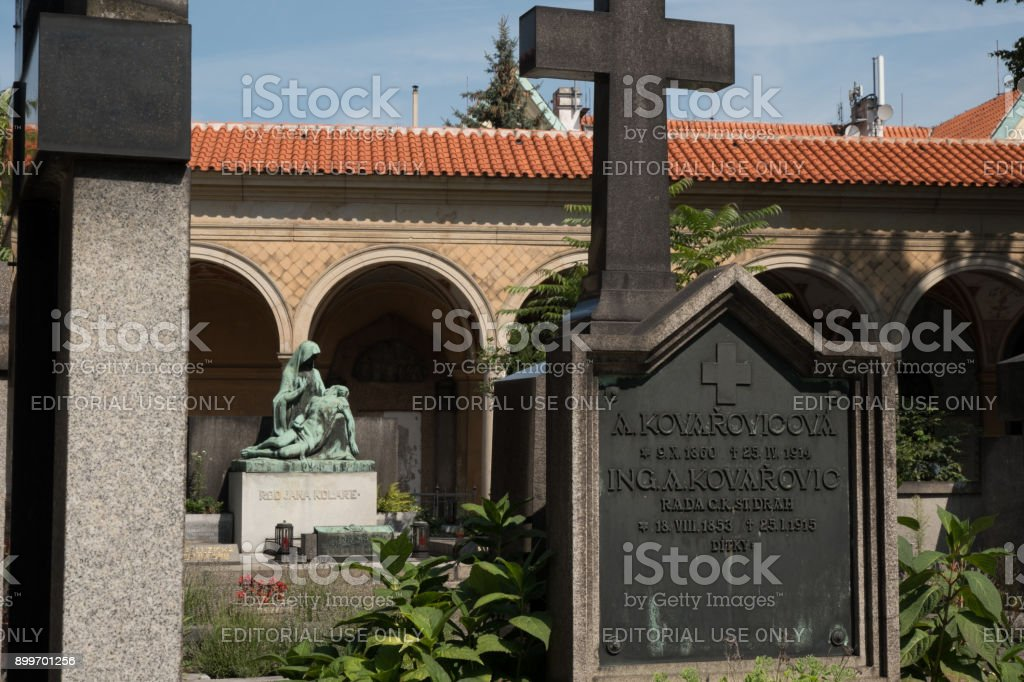 Bronze Pieta of the Mother Mary and the dead Jesus in the Vysehrad Cemetery in Prague behind a stone grave with a cross on top from 1915 in Vysehrad Cemetery. stock photo