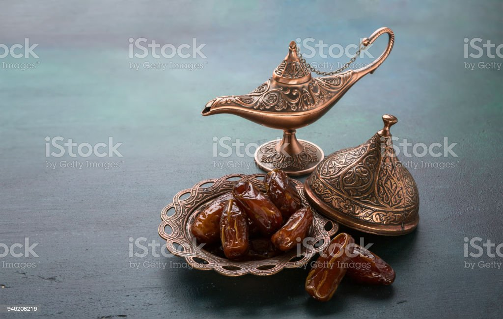 Bronze plate with dates  and aladdin lamp on dark green wooden background. Ramadan background. Ramadan kareem. stock photo