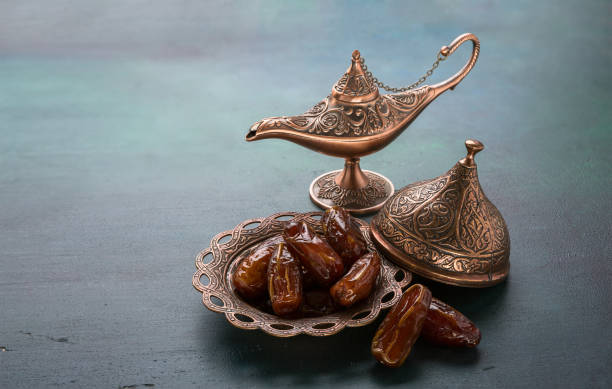 bronze plate with dates  and aladdin lamp on dark green wooden background. ramadan background. ramadan kareem. - ramadan stock photos and pictures