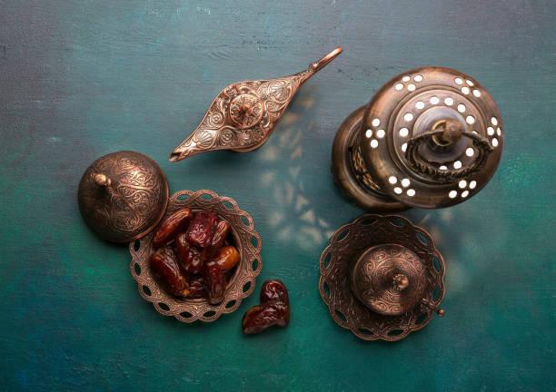 bronzetafel mit terminen, kaffeetasse, arabische laterne und aladdin lampe auf hölzernen dunkelgrünen hintergrund. ramadan kareem.  ramadan-hintergrund.  flach zu legen. - arabeske stock-fotos und bilder