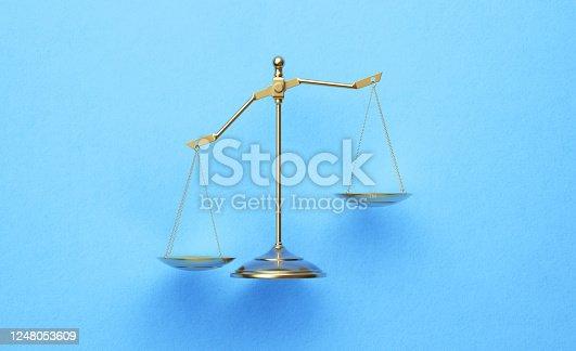 824305956 istock photo Bronze Scale over Blue Background 1248053609