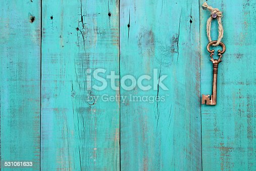 Bronze skeleton key hanging by rope on antique teal blue distressed wood door