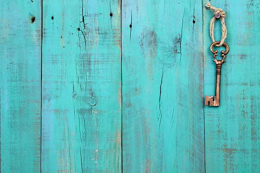 Bronze skeleton key hanging on antique teal blue wooden background