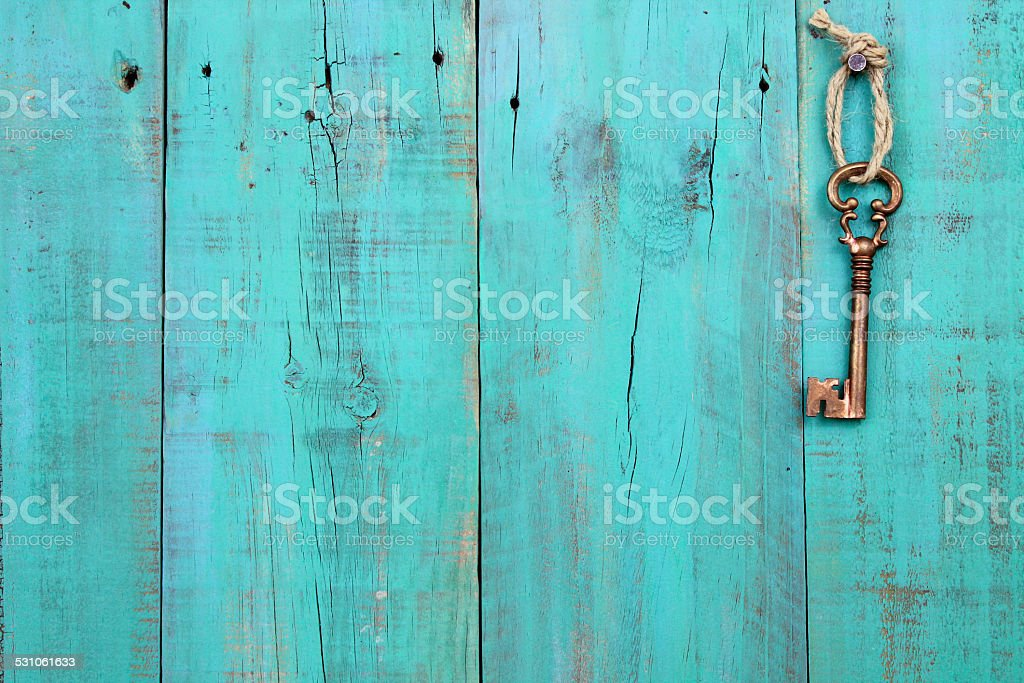 Bronze skeleton key hanging on antique teal blue wooden background stock photo