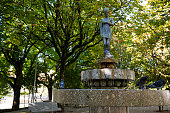 Bronze statue of a girl in the middle of a city garden. Fountain with pigeons taking a bath on a hot day. Alameda gardens. Guimarães, Portugal.