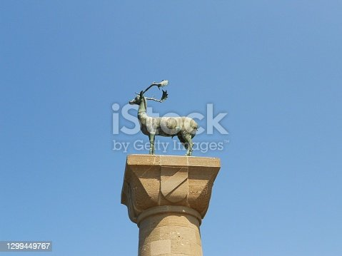 istock Bronze statue of deer at the entrance to Mandraki Harbour in Rhodes towards the blue sky 1299449767