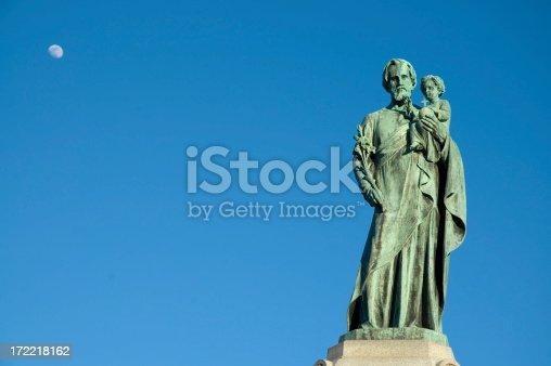 Statue of Saint Joseph holding Jesus over a blue sky.