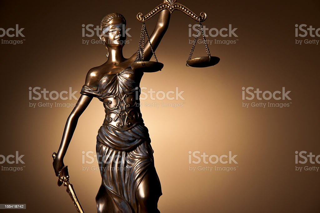 Bronze statue of Themis on a gold background stock photo
