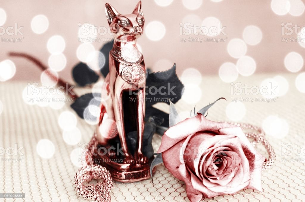 Bronze statuette of Bastet with a beautiful pink rose on a gold grid with bokeh effect stock photo