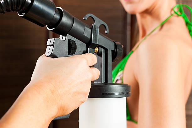 Bronzing in cosmetic studio Beautician (only hands to be seen) with airbrush-pistol and client in a cosmetic studio doing bronzing airbrush stock pictures, royalty-free photos & images