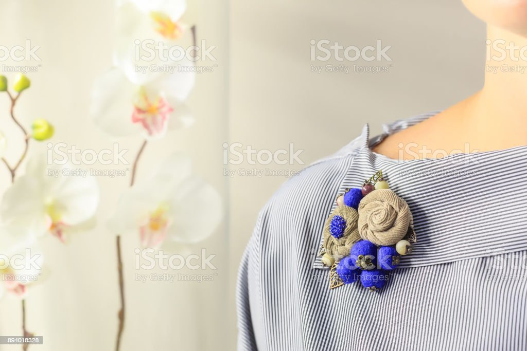 Brooch handmade in the form of flowers beige and blue color is attached to the female blouse stock photo