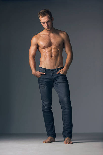Brooding masuclinity Full-length studio shot of a bare-chested muscular man wearing jeans shirtless male models stock pictures, royalty-free photos & images