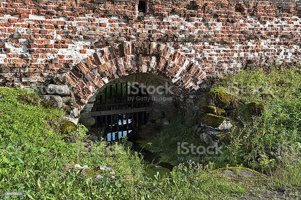 Brook flowing through the wall of an ancient monastery royalty-free stock photo