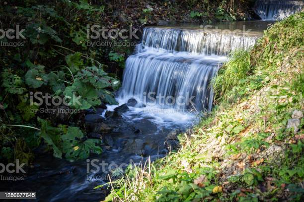 Photo of A brook with small waterfall in motion blur