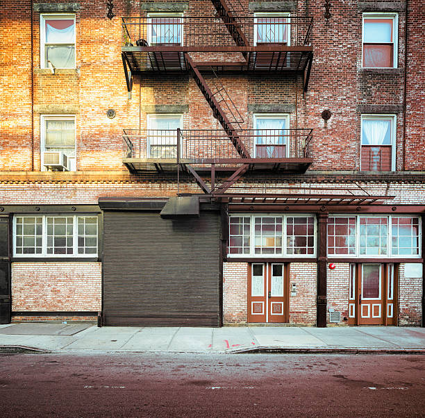 Brooklyn apartment buildings facade with large steel garage door Brooklyn apartment buildings facade with large steel garage door and fire escape stairs. alley stock pictures, royalty-free photos & images