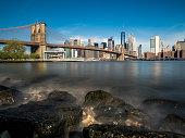 Brooklyn bridge and Manhattan at sunny day, NYC, USA. Long exposure shot.