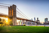 View of Brooklyn Bridge and Lower Manhattan at sunset with sun Flare and a blank space