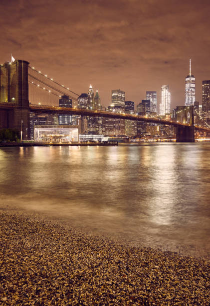 Brooklyn Bridge and New York City skyline at night, color toning applied, USA. stock photo