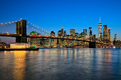 Brooklyn Bridge, East River, and Lower Manhattan, New York skyline illuminated at dusk, HDR image.