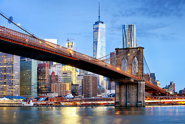 brooklyn bridge and wtc freedom tower at night, new york - international landmark stock photos and pictures