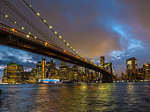 sunset over the East river, Manhattan and Brooklyn bridge. The freedom tower is in the clouds