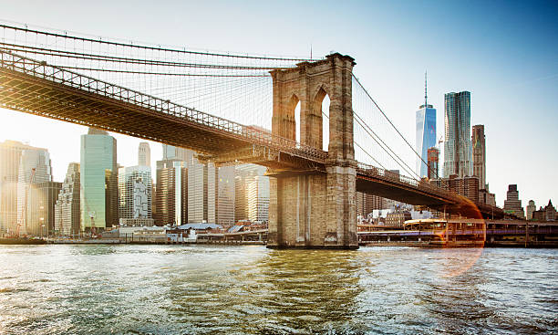 brooklyn bridge from east river sunset with flare - wall street lower manhattan stock pictures, royalty-free photos & images