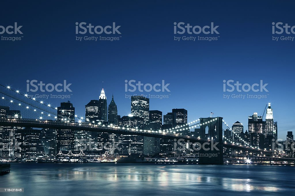 Brooklyn Bridge in front of pretty Manhattan skyline at dusk stock photo