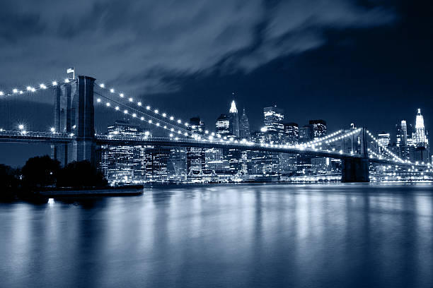 Brooklyn Bridge in New York with lights reflections on water stock photo