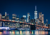 A long exposure of New York City Brooklyn Bridge at night featuring skyscrapers, stars in the Sky and the World Trade Centre and the East River