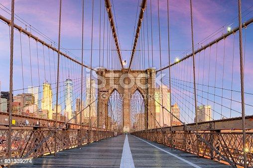 New York, New York on the Brooklyn Bridge Promenade facing Manhattan's skyline at dawn.