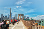 Brooklyn bridge. Beautiful sunny day, walking people, Manhattan skyscrapers on background\nNew York City/USA - May 26, 2019