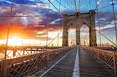 Brooklyn Bridge over East River viewed from New York City Lower Manhattan waterfront at sunset.